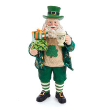 """Show off your Irish pride with this 10.5-in Fabriche Musical Irish Santa With Coffee Mug from Kurt Adler! This table piece features Santa in green clothes with gold detailing. Shamrocks can be seen throughout. In his left hand is a mug that reads """"Irish Coffee"""". Gifts are stacked on his right hand. This table piece is the perfect addition to any St. Patrick's Day or Irish themed holiday decoration!"""