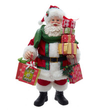 Tis the season of giving. Celebrate with this 11.5-in Fabriche Red and Green Traditional Gifts Santa from Kurt Adler! This table piece features Santa with gift bags and wrapped presents. He is wrapped in a green scarf with green and holly berry detailing on his Santa hat. A fun and whimsical addition to any holiday decoration!