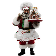 """This 10.5-in Fabriche Black Chef Santa from Kurt Adler is perfect to celebrate the baker in your life! Santa is wearing a """"Merry Christmas"""" apron decorated with red trim and a matching chef's hat while carrying a decorated gingerbread house in one hand and a gingerbread cookie in the other hand. This is a perfect addition to any holiday decor."""