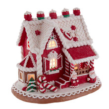 Add a sweet touch to your holiday decoration with this Kurt Adler 9-in Red and White Santa and Mrs. Claus Gingerbread House! This table piece is decorated using the classic Christmas colors: red and white. Mr. and Mrs. Claus stand at the front of the house greeting guest with their cheery smiles! When switched on, the house is illuminated from within.