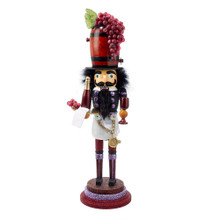 """This Kurt Adler 19"""" Hollywood Wine Nutcracker is a fun, festive way to add to your holiday decoration or nutcracker collection! Designed by renowned artist Holly Adler, Hollywood Nutcrackers is a whimsical collection of nutcrackers created exclusively for Kurt S. Adler, Inc. and features an assortment of designs including Christmas, fantasy and everyday nutcrackers. Their designs put a unique, vibrant, memorable twist on traditional nutcrackers. Like all Hollywood Nutcrackers, this nutcracker represents Christmas in a unique, glittery way. Perfect for wine lovers, his hat is a wine barrel topped with realistic purple grapes; his outfit has a wine-Colored theme, with shades of purple, red, gold, and black. He is holding in one hand a serving tray with purple grapes, a bottle of red wine, and a napkin, and in the other hand he is holding a purple wine glass."""