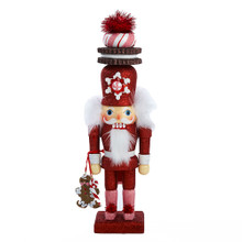 """This Kurt Adler 12"""" Hollywood Red Gingerbread Nutcracker with Cookie Hat is a fun, festive way to add to your holiday decoration or nutcracker collection. Designed by renowned artist Holly Adler, Hollywood Nutcrackers is a whimsical collection of nutcrackers created exclusively for Kurt S. Adler, Inc. and features an assortment of designs including Christmas, fantasy and everyday nutcrackers. Their designs put a unique, vibrant, memorable twist on traditional nutcrackers. This cute nutcracker comes dressed in a fully glittered red and pink suit. He comes with tasty accents like a peppermint and cookie topped hat and holds a dangling gingerbread man. Metallic red poof balls further add whimsy to this fun piece."""