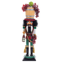Designed by renowned artist Holly Adler, Hollywood Nutcrackers is a whimsical collection of nutcrackers created exclusively for Kurt Adler. This piece features a vineyard-inspired design, with details like grapes, a bottle of wine, and a wine barrel hat.