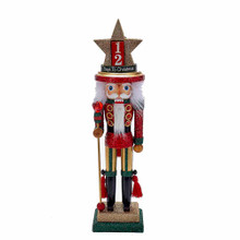 """Designed by renowned artist Holly Adler, Hollywood Nutcrackers is a whimsical collection of nutcrackers created exclusively for Kurt Adler. This piece features a nutcracker wearing red, green and gold. For an extra special touch, his hat has two sides: one side has two numbered blocks that you can arrange to Countdown the days until Christmas and the words """"Days to Christmas."""" The second side features a beautiful Nativity scene, to remind you of the true meaning of Christmas."""