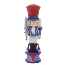 Hollywood Nutcrackers is a whimsical collection of nutcrackers created exclusively for Kurt S. Adler, Inc. and features an assortment of designs that put a unique, vibrant, memorable twist on traditional nutcrackers. This 15-in Hollywood Nutcracker Prince from Kurt Adler is a fun and festive addition to any holiday decor or nutcracker collection. Featuring the Nutcracker Prince from the Nutcracker, this piece is wearing rich, vibrant shades of red, blue, and purple, and is holding a sword.