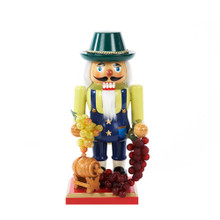"""This Kurt Adler 10.25"""" Wooden Winemaker Nutcracker is a beautiful, festive way to add to your holiday decoration or nutcracker collection, especially if you are a wine-lover! The winemaker featured in this item is wearing star-adorned blue overalls, a green hat, and is holding two bunches of grapes: one green, and one purple. At his feet is another bunch of purple grapes and a small wooden wine barrel. He is standing on a red and gold base."""