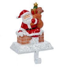 Hang your stocking by the chimney in style! This resin Santa with gift box stocking hanger from Kurt Adler features a fun scene of Santa Claus getting ready to climb down a brick chimney to deliver a bag full of toys. A glittery, snowy base lends an extra festive touch.