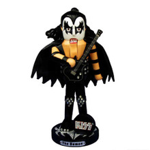 """This Kurt Adler 11"""" KISS Demon Nutcracker is a fun way for any KISS fan or nutcracker collector to add to their holiday decoration or collection! Resembling Gene Simmons as his stage alter-ego, The Demon, this nutcracker has long hair, the trademark black and white makeup, a black demon-wing cape, a black rhinestone-adorned outfit, and black boots. He is suitably holding a black bass guitar, and is standing on a black and silver stand with a plaque that says """"The Demon"""" and a small black and silver KISS logo sign."""