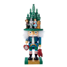 """Fly over the rainbow with this Kurt Adler 16"""" Wizard of Oz Hollywood Nutcracker. Perfect for your holiday decoration and for fans of the Wizard of Oz, this piece features a nutcracker in green and blue glittered attire with red and white striped socks and a rainbow painted on his shirt. His white hair is covered with a green hat that is depicted as the Land of Oz with the Scarecrow, Tin Man, Dorothy, and the Cowardly Lion in front of it. This will make a wonderful addition to anyone's nutcracker collection!"""