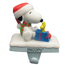 Hang your stocking by the chimney in style with Kurt Adler's Snoopy and Woodstock stocking hanger. Features the adorable Snoopy bundled up for the winter, opening a present - only to find his best friend, Woodstock, within!