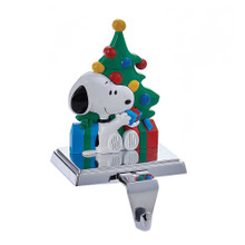 Hang your stocking by the chimney in style with Kurt Adler's Snoopy stocking holder. The adorable Snoopy is showcased in front of a decorated Christmas tree with presents while holding and inspecting one of the presents himself. This stocking holder also has a retractable hook for convenience.