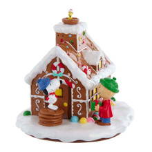 This B/O Peanuts© LED Gingerbread House Table Piece from Kurt Adler is a fun, festive way to add to your holiday decoration or display. The festive gingerbread house depicts Snoopy and Charlie Brown holding presents around a decorated gingerbread house. Woodstock is sitting in a nest at the top of the chimney.