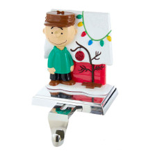 This 5-in Peanuts© Charlie Brown with Doghouse Stocking Holder from Kurt Adler is a fun, festive way to add to your holiday decoration or display. The stocking holder features Charlie Brown with a doghouse standing next to a bent tree with an oversized ornament, decorated for the holidays. This stocking holder also has a retractable hook for convenience.