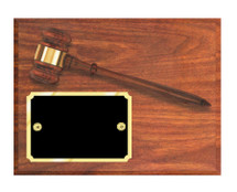 A walnut finish plaque with attached gavel