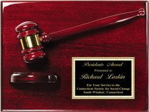 A rosewood piano finish plaque with gavel and stand