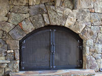hand forged retrofit fireplace doors with arched craftsman grid