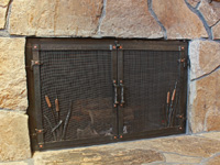hand forged fireplace doors with cat tail accents