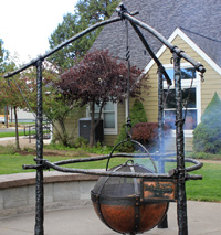 Hand forged fire pit with copper cauldron, iron logs tied with hand forged knots and rope