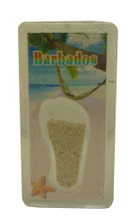 A magnet with an image of a beach in Barbados and some Barbados sand.