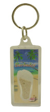 A keychain with an image of a beach in Barbados and some Barbados sand.