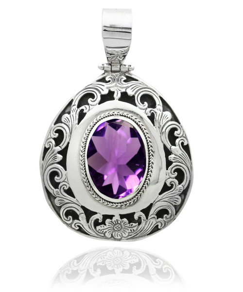 A chic and stylish oval pendant featuring a large center stone in textured sterling silver filigree style and setting.