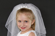First communion is a special time in a person life. When it is time for your little girl's first communion, make sure they are ready! This pearl and satin veil can complete the look for her special day. This veil has a built in comb, for a strong hold in your little girl's hair.  Pearls, flowers, and beads are used to add a beautiful touch to the quality satin. This veil will frame your daughter's face, perfect for pictures.