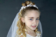 First Holy Communion Crystal Flower headband with veil. Veil is made of satin and crystal flowers with pearl leaves adorn the wreath. The back of the wreath has a satin flower and a ribbon bow and two layers of tulle.