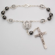 St Benedict Hematite Auto Rosary. 7MM hematite beads with silver oxidized crucifix and center. Comes on a hang tag.