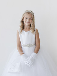 This ankle length communion dress has a satin bodice attached to a tulle skirt. The buttons down the back of the dress are covered with satin.