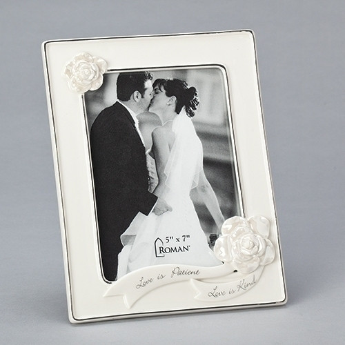 """8.75""""H White Porcelain Wedding or Anniversary Photo Frame adorned with decorative flowers and the words Love is Patient and Love is Kind on banners across the bottom of the frame.  Frame holds 5"""" x 7"""" photo. Frame is made of porcelain and measures 8.75""""H X 6.75""""W X .75""""L."""