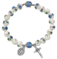"""7 1/2"""" Adult Blue Ceramic Flower Crystal Stretch Bracelet.  Aqua flower beads with aqua crystal bead stretch bracelet Miraculous medal and crucifix are oxidised silver. Bracelet comes carded.  Made in the USA!"""