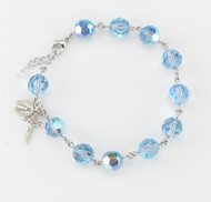 10mm Round Faceted Swarovski  Light Sapphire Rosary Bracelet. Sterling silver miraculous medal and crucifix with sterling silver links or rhodium plated brass links. Comes in a deluxe velour gift box. Made in the USA.