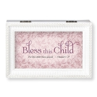 "Bless This Child White and Pink Music Box.  The lid has the words ""Bless this Child~for this child I have prayed.""  Music Box plays ""Jesus Loves Me."" Measurement: 6.125""L X 4""W X 2.625""H. Made of Plastic and Metal"