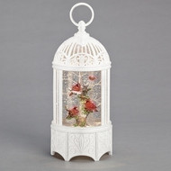 A white birdcage filled with three cardinals resting on different branches.