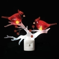 Night light that features a white branch and two red cardinals on the branch.
