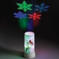 Plastic projector candle with cardinals painted on side and snowflakes projected on the ceiling.