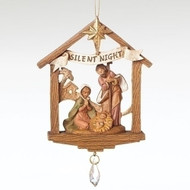 Christmas ornament featuring the Holy family in a stable, a banner that reads 'Silent Night', and a dangling crystal.