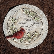 "Cardinal Memorial Stepping Stone. The stepping stone measures 10.25"" in diameter. The Cardinal Memorial Stone is made of a resin stone mix. On the stone is written: ""When a cardinal appears an angel is near."" On the stone is depicted a cardinal sitting on branches with green leaves"