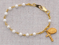"""This bracelet has 4mm glass pearl beads and a gold plated pewter crucifix and mircaulous medal charms attached. Comes in a gift box. Measures 5 1/2""""."""