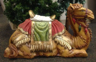 Highly decorated camel lying on the ground with a saddle stool.