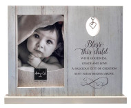 """Bless This Child Photo Frame features a pewter finsih heart charm. Frame holds a 4"""" x 6"""" photo. Measurements are 7 1/2"""" x 9 1/2"""". Made of MDF. Comes boxed.  """"Bless this child with goodness, grace and love. A precious gift of creation sent from heaven above."""""""