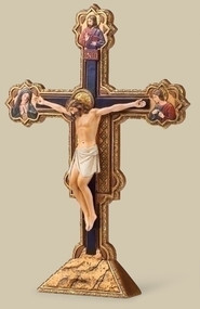 "10.5"" Ognissanti Standing Crucifix. Resin/Stone Mix. 10.5""H x 7.38""W x 1.25""D. The Ognissanti (All Saints) crucifix, is the work of the 14th-century Italian master Giotto.  For years the 16.4 foot crucifix had been left in a side room of a church, unseen.  This beautiful work of art was returned to the Ognissanti church in Florence in 2010 after ten years of restoration."