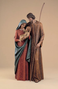 Colored sculpture of Virgin Mary being embraced by Saint Joseph, holding Child Jesus.