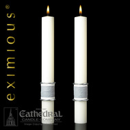 Two white altar candles with silver/grey wrap around the bottom.
