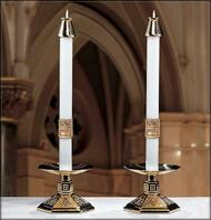 Two white candles on golden stands with golden candle tips.
