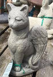 """This cement guardian angel cat statue is a unique and beautiful addition to your garden. This statue features a cat sitting with its wings open. Details: Dimensions: 13.75""""H x 7.5""""W x 8""""L 14 lbs Natural color Made to order. Allow 4-6 weeks for delivery. Made in the USA"""