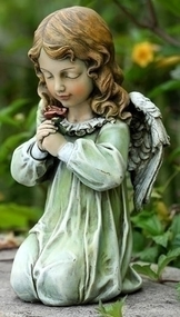 Statue of a little girl angel kneeling and holding a flower.