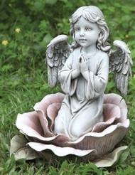 Angel kneeling in a rose garden statue.