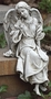 Statue of angel sitting on a ledge looking left.