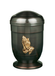 "Copper Urn has a Dark Finish and Praying Hands Medallion. Heights: 11 3/4"". Minimum Capacity of 200 Cubic inches."